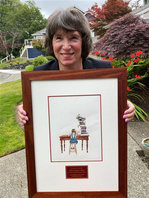 """Representative Laurie Dolan holding framed artwork """"Toppling Books"""""""