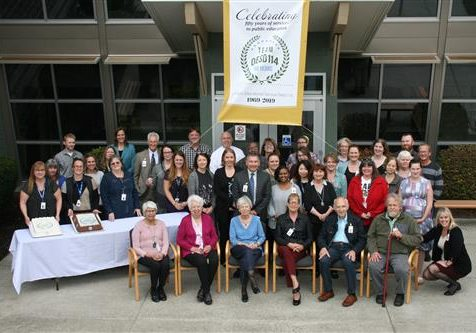 OESD Board of Directors, Superintendent, and Staff Gathered for a Photo on September 20, 2018, with celebration banner & cake