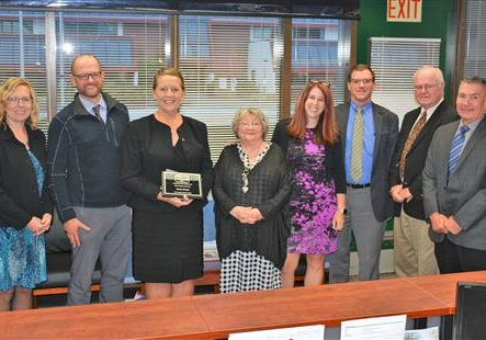 Teacher of the Year Karen Doran holding her award plaque.  Pictured with Board Members, Principal, PA Supt, OESD Supt