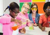 four students participating in science, mixing colorful solutions